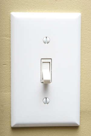 power switch: A closeup shot of a modern light switch on an interior wall.