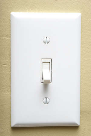 switch on the light: Un disparo de cerca de un interruptor de la luz moderna en una pared interior. Foto de archivo
