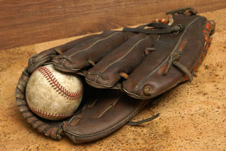 leather glove: A low contrast image of a well used hardball and glove for those who love the sport of baseball. Stock Photo