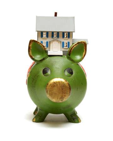 equidad: Una casa en miniatura se basa en una alcancía para los conceptos monetarios. Foto de archivo