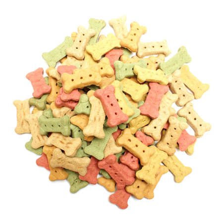 An overhead shot of a pile of bone shaped dog treats isolated on white.