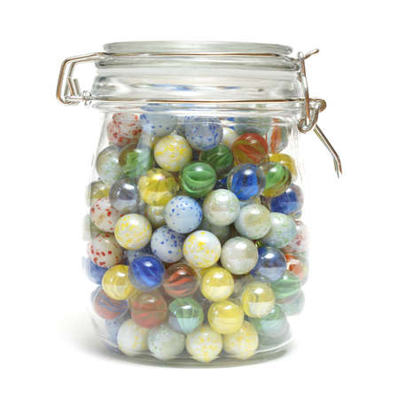 A glass jar is full of various marbles. Archivio Fotografico