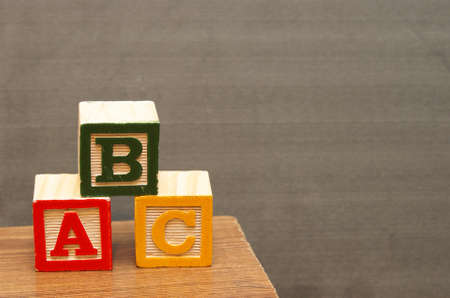 Alphabet blocks in front of the chalkboard for learning the basics of the english language. photo