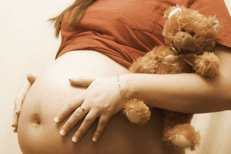 girl belly: A pregnant mother holds her childs teddy bear. Stock Photo