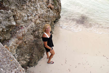 A woman stands at the beach with this high angle shot.
