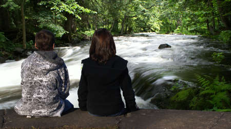 Two young children are sitting by the creek to enjoy the natural beauty. photo