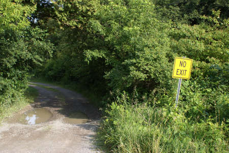 A bright yellow sign warns drivers that the road ahead has no exit.
