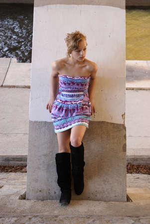 innocent girl: A young girl poses on a joyce under a bridge.