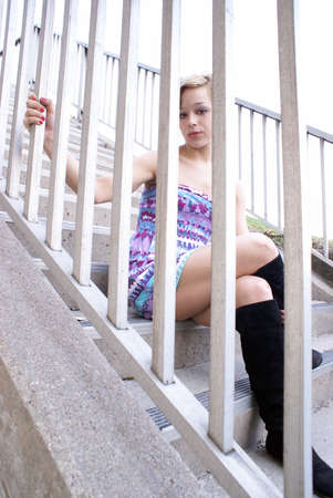 A young adult sits on the concrete stairs in her fashionable dress and boots.