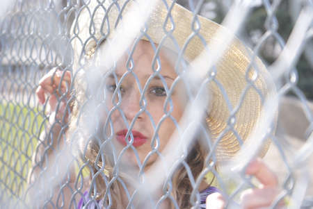 A woman is confined to the chain link fence.
