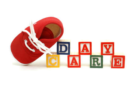 An infants shoe next to the words day care. Stock Photo - 13513435