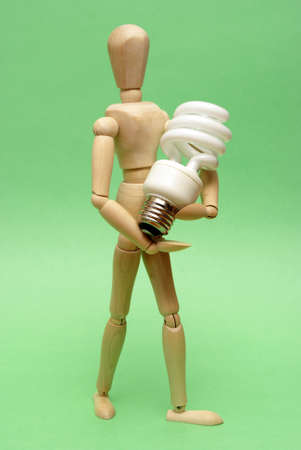 wooden doll: A wooden guy holds onto a modern cfl lightbulb for many ecological concepts. Stock Photo