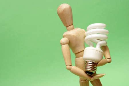 A wooden guy holds onto a modern cfl lightbulb for many ecological concepts. Reklamní fotografie