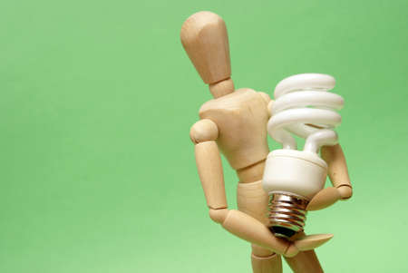 A wooden guy holds onto a modern cfl lightbulb for many ecological concepts. Stock Photo - 13513446