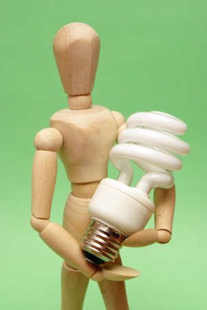 A wooden guy holds onto a modern cfl lightbulb for many ecological concepts. Stock Photo - 13735469