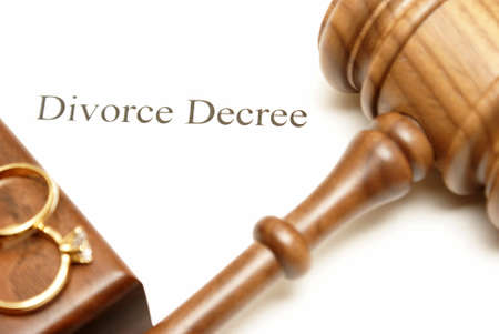 decree: A gavel and wedding rings on top of divorce papers with the focus on the writing.