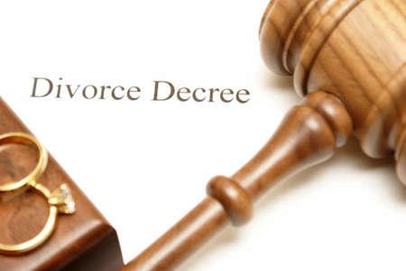 Een hamer en trouwringen op de top van scheidingspapieren met de focus op het schrijven.