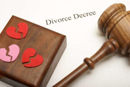 Een hamer en gebroken harten op de top van scheidingspapieren met de focus op het schrijven. Stockfoto