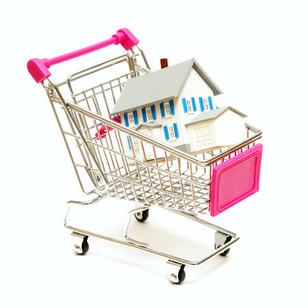 A house sits inside a shopping cart for real estate concepts. photo
