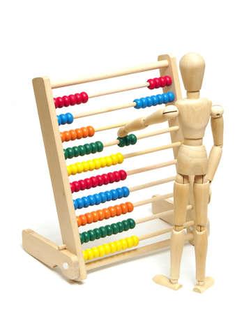 juguetes de madera: Un maniquí coloca unas cuentas en el ábaco para resolver su tarea de matemáticas.