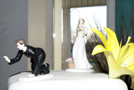 topper: A comedic wedding cake topper of the bride catching her husband with a fishing line.