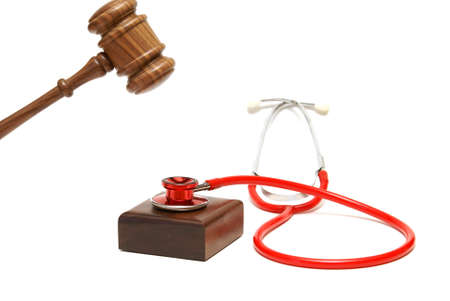 A gavel is about to hammer down on a stethoscope that is resting on the sounding block.
