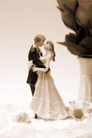 A wedding cake topper in a sepia toned image.