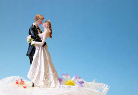 A wedding cake topper on top of the newlyweds dessert.