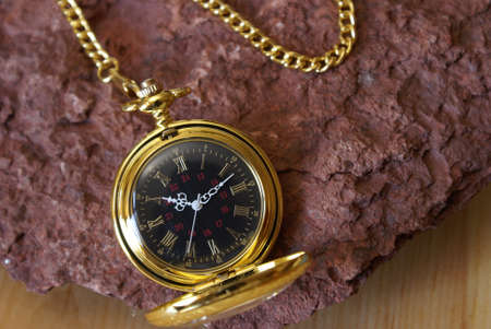 hand chain: A gold pocket watch on a red sandstone. Stock Photo