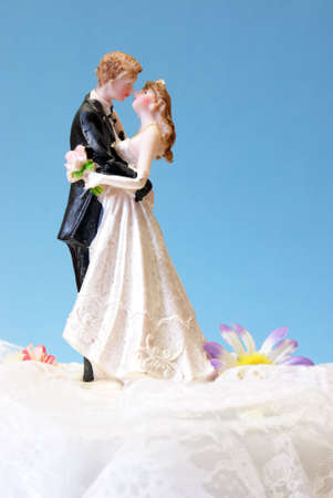 topper: A wedding cake topper on top of the newlyweds dessert.