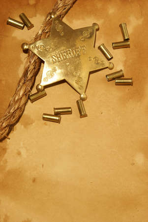 A sheriff badge and gun shells on some antique paper. photo