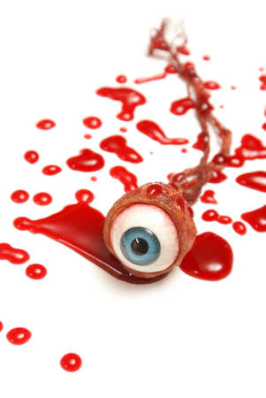A realistic looking eyeball in a pool of blood over a white background. photo