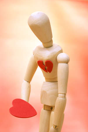 wooden mannequin: A mannequin looks down to their newly found mended heart. Stock Photo