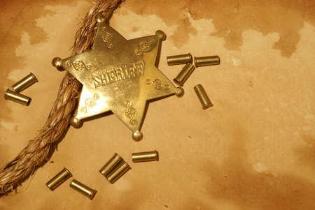 sheriff badge: Una insignia de sheriff y un arma conchas en un poco de papel antiguo.