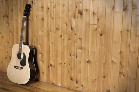 A vintage styled image of a classic acoustic guitar leaning on a wooden wall. photo