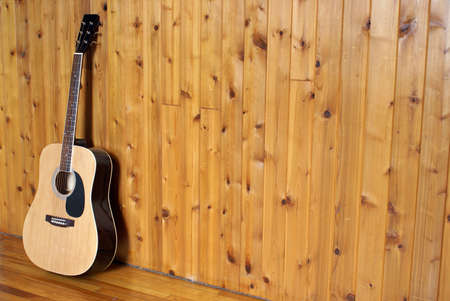 A classic acoustic guitar leaning on a wooden wall. photo