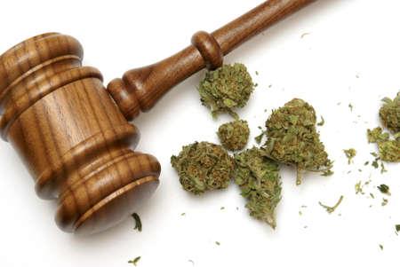 Marihuana en een hamer samen voor veel juridische begrippen op de drug.