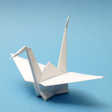 A nicely folded origami swan over a blue tranquil background. photo