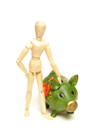 wooden mannequin: A mannequin stays close to his pig bank for financial concepts.