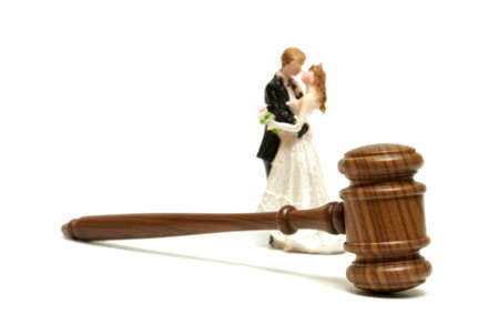A gavel with a bride and groom cake topper represent marriage legalities.