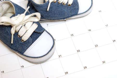 多くのスケジューリングの表現のためのカレンダーの赤ちゃんの靴。 写真素材