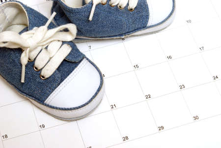 Baby shoes on a calendar for many scheduling representations.