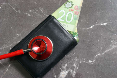 doctor money: A medical stethoscope checks the wellbeing of someones wallet.