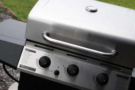 grill: A brand new stainless steel bbq being used for the first time to welcome the summertime gatherings.