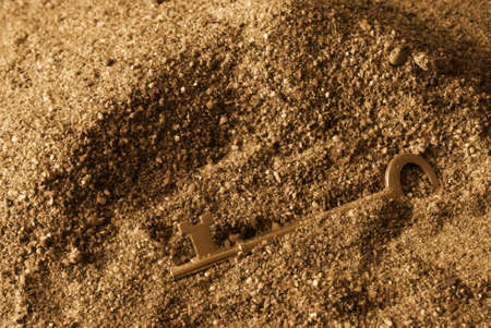 lock and key: A skeleton key is found in the sandy ground to which one wonders what its secrets hold.