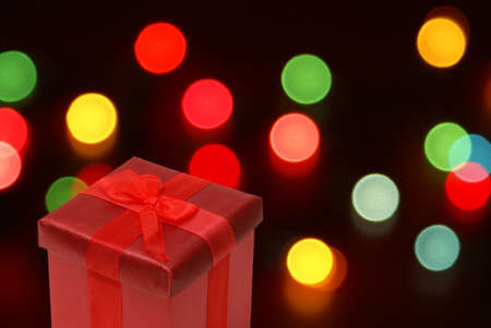 a red present with christmas lights blurred in the background stock photo 20748396