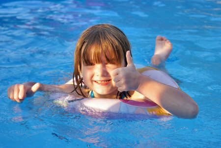 A happy five year old girl enjoys her summertime in the pool. Stok Fotoğraf