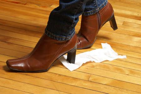 papel higienico: Una mujer sigue sin saberlo, un trozo de papel higiénico en la parte inferior de la bota que lo convierte en un tiempo bochornoso. Foto de archivo