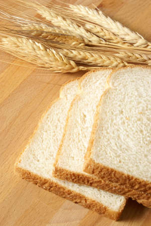 has been: A closeup of some fresh baked bread that has been sliced on a wooden board.