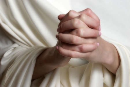 white robe: A young woman faithfully brings her hands together in essence of prayer.